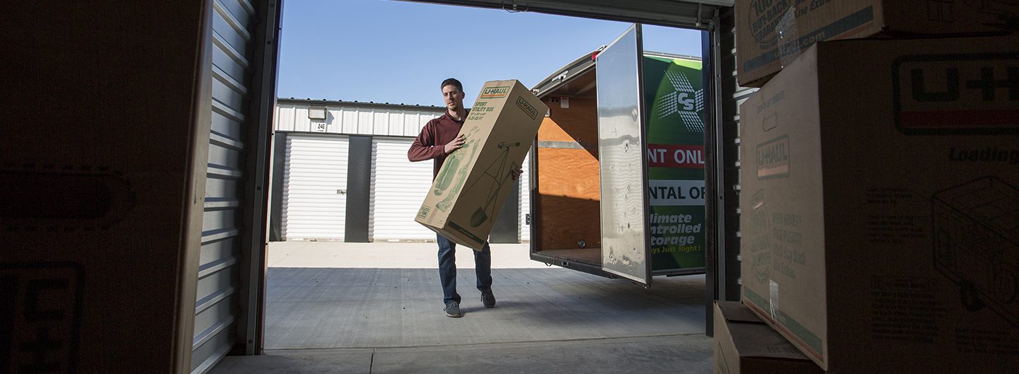 A man carries a large box into a storage unit at Citywide Storage in Salina, Kansas.